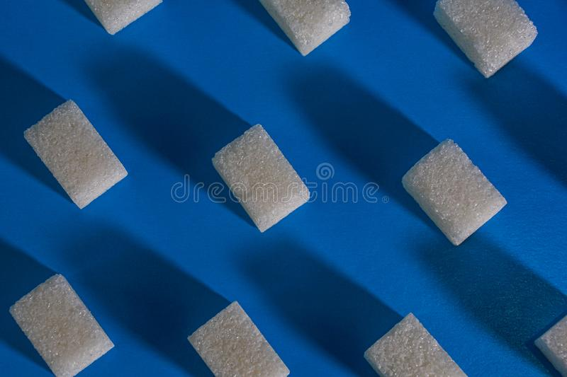 Sugar cubes on a blue background. Abstract background royalty free stock photography