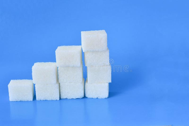 Sugar cubes with syringe. Diabetes concept. The concept of possible harm from sugar. Increase in blood sugar levels, the graph of. Sugar cubes. The concept of stock photo