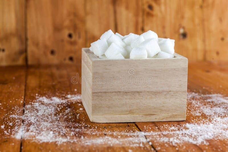Sugar Cubes dans la place a formé la cuvette avec la flaque de sucre centrifugé plus d'à l'arrière-plan en bois photos stock