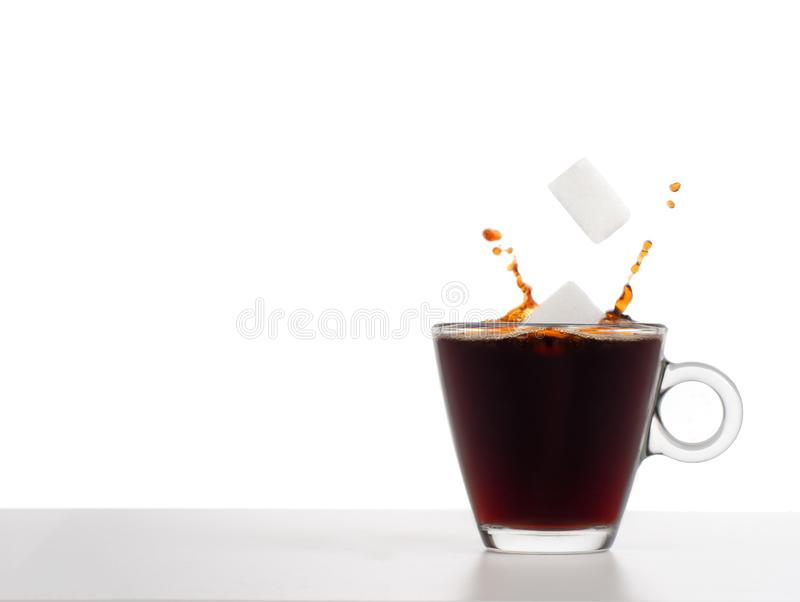 Sugar cubes falling into coffee with splash, health concept. Plain background for copyspace. Glass cup. Sugar falling into coffee with splash, health concept stock photos