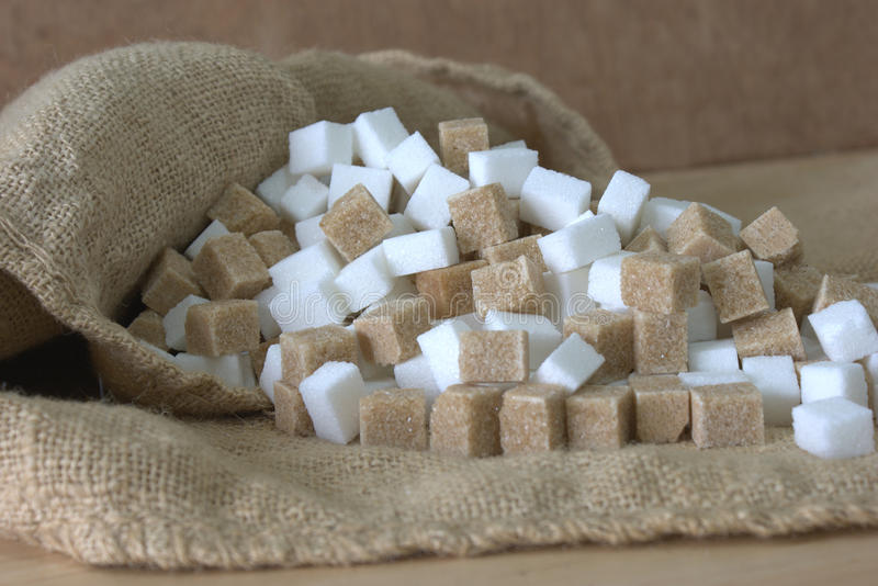 Sugar cubes in a hessian sack. Hessian sack of mixed brown and white sugar cubes stock photography