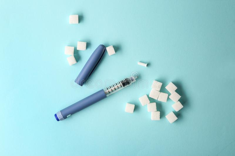 Sugar cubes and insulin syringe on color background. Diabetes concept royalty free stock images