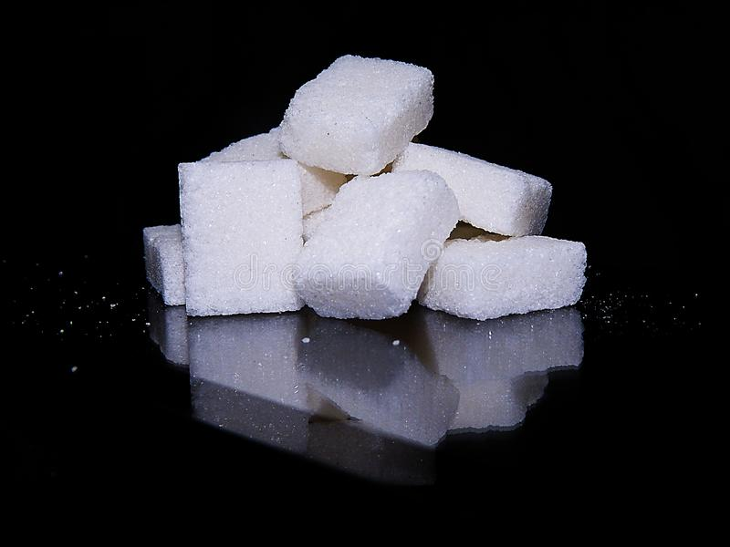 Sugar cubes isolated in black background. Sugar cubes isolated on a black reflective background refined ,eating group lump isolated square sweetener close stock photos