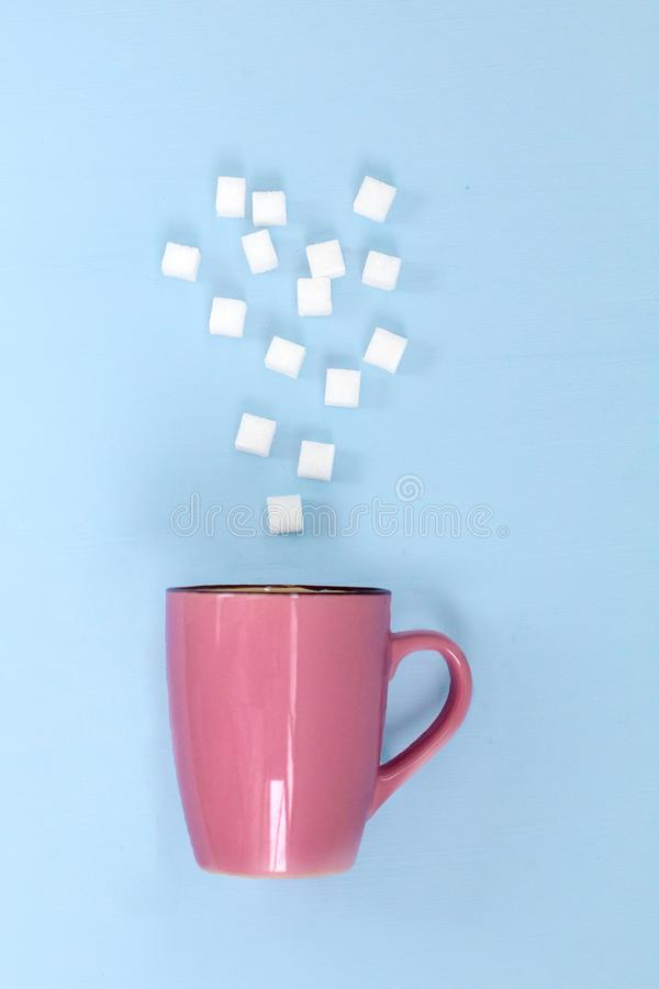 Sugar cubes levitation falling to the pink cup. Art healthy food and lifestyle concept stock image