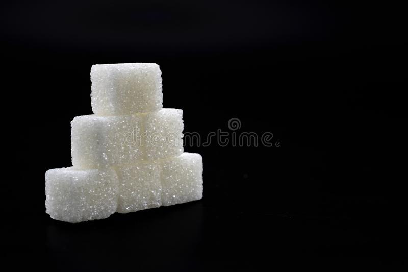 Sugar cubes lined up in pyramid shape. Black background white isolated food sweet group pile heap unhealthy lump space copy energy diet ingredient crystal stock photography