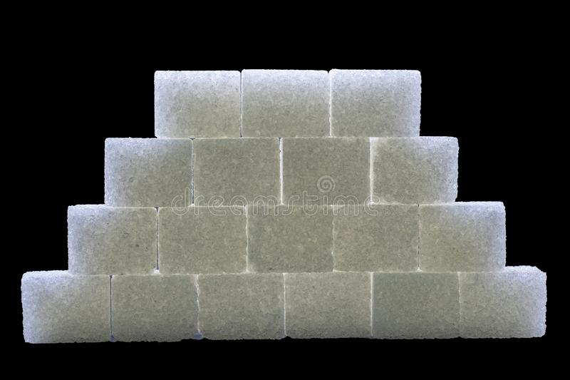 Sugar cubes lined up in pyramid shape. Black background white isolated food sweet group pile heap unhealthy lump space copy energy diet ingredient crystal royalty free stock image