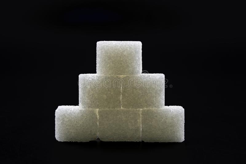 Sugar cubes lined up in pyramid shape. Black background white isolated food sweet group pile heap unhealthy lump space copy energy diet ingredient crystal stock photo