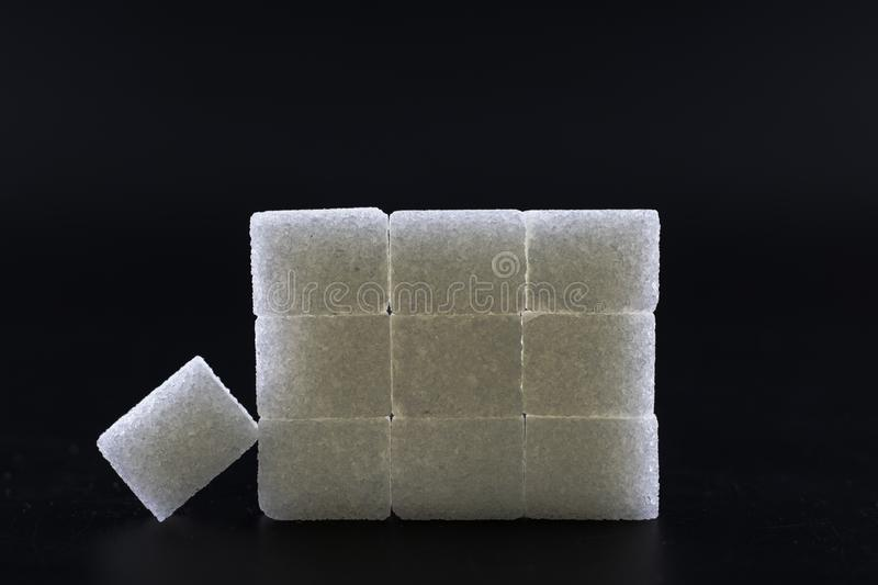 Sugar cubes lined up in pyramid shape. Black background white isolated food sweet group pile heap unhealthy lump space copy energy diet ingredient crystal royalty free stock images