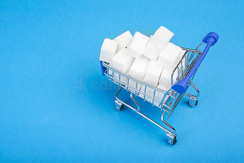 Sugar cubes. A mountain of sugar in the shopping cart on blue background. Top view. royalty free stock photos