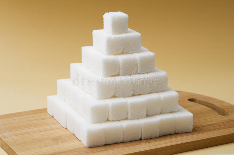 Sugar cubes pyramid. On a yellow basckground stock image