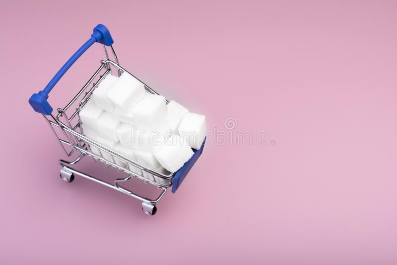 Sugar cubes. Shopping cart with write sugar cubes isolated on pink background. Sugar concept. Top view stock images