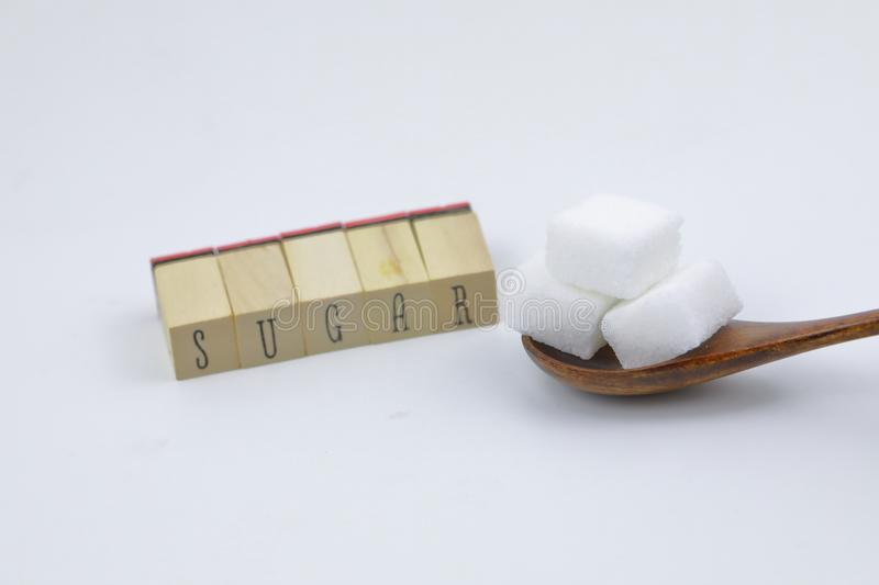 Sugar cubes three sugar cubes on a wooden spoon sugar letter character on white background stock image