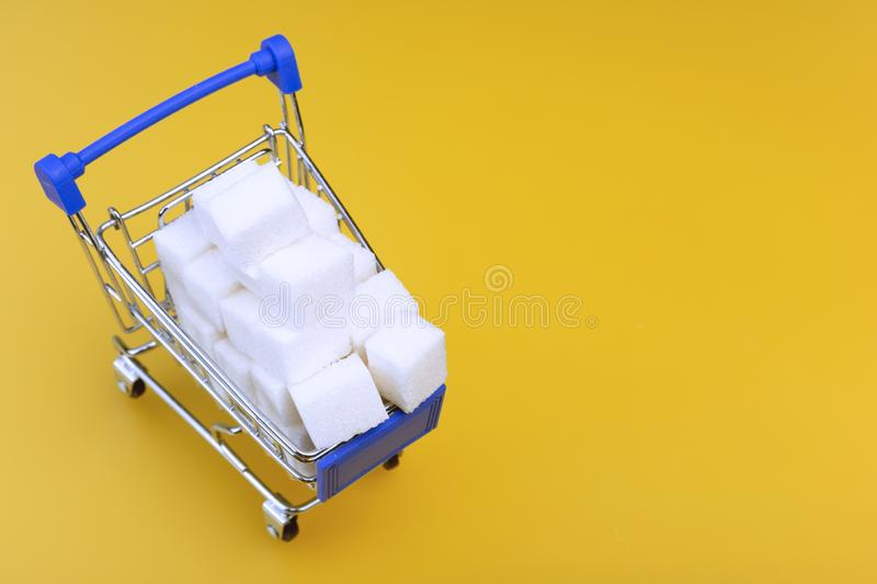 Sugar cubes. White sugar cubes in a shopping cart, isolated on yellow background. Copy space for text royalty free stock image