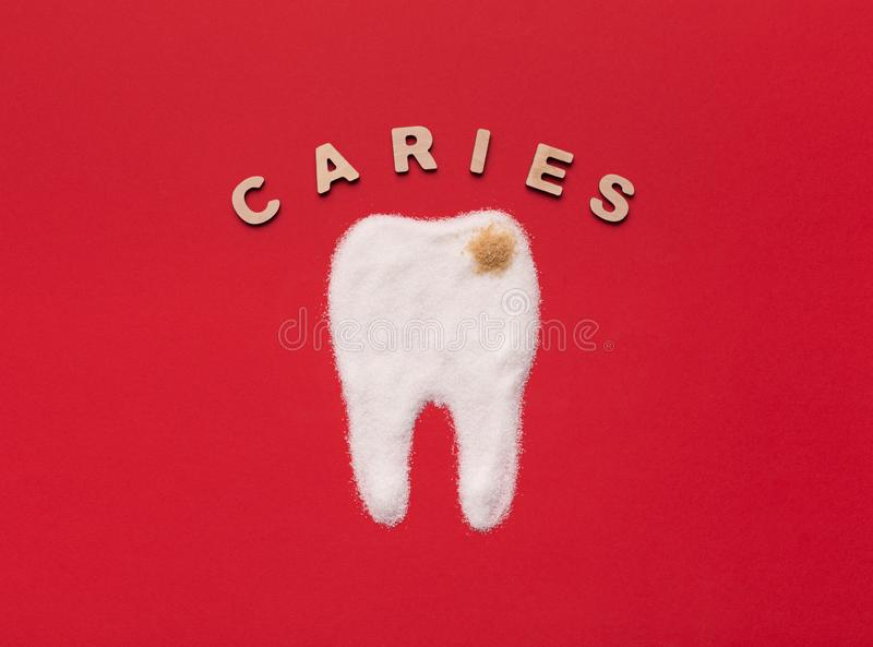 Sugar destroys tooth enamel and leads to caries. Sugar destroying tooth enamel and leading to caries. Tooth with decay made from white and brown sugar on red stock images