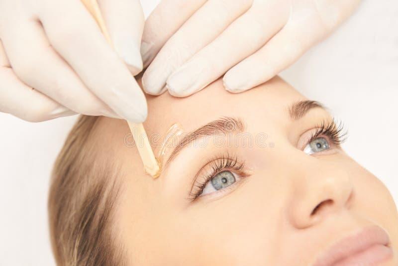 Sugar hair removal from woman body. Wax epilation spa procedure. Procedure beautician female. Eyebrow stock image