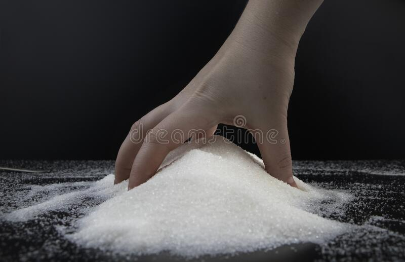 Sugar in hand on a black background. The concept of addiction to sweets. Macro photo of granulated sugar. Sugar in hand on black background. The concept of stock photos