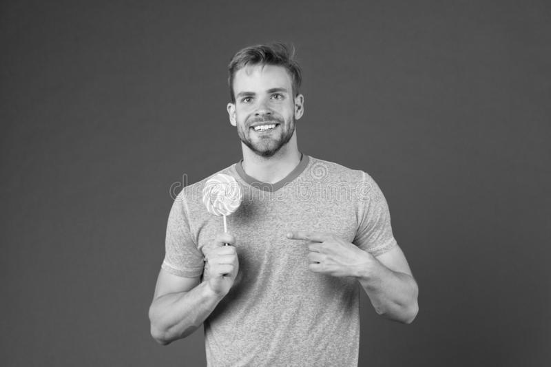 Sugar harmful for health. Guy hold lollipop candy violet background. Man handsome macho eat big colorful sweet lollipop stock photos