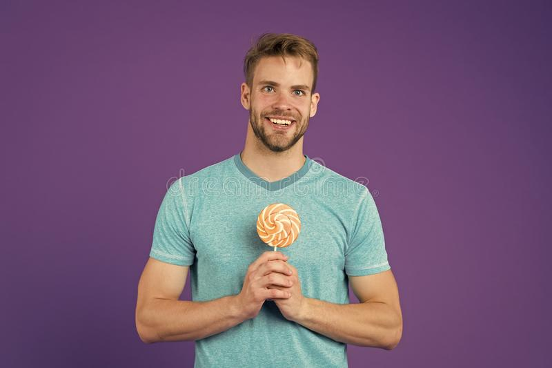 Sugar harmful for health. Guy hold lollipop candy violet background. Man handsome macho eat big colorful sweet lollipop stock photography