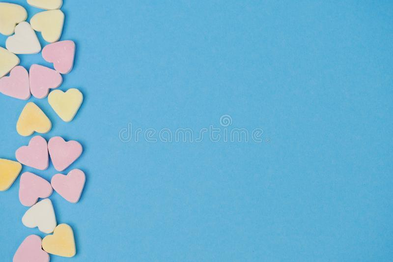 Sugar hearts on the left side on blue background for text royalty free stock photos