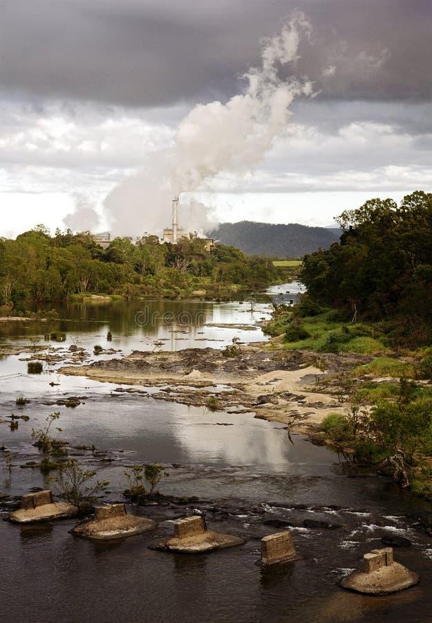 Sugar Mill Puffing Smoke Across uma angra fotografia de stock
