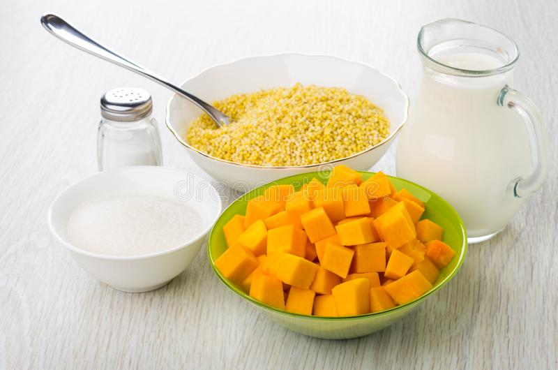 Sugar, millet, spoon in bowl, pumpkin in bowls, salt, milk royalty free stock image