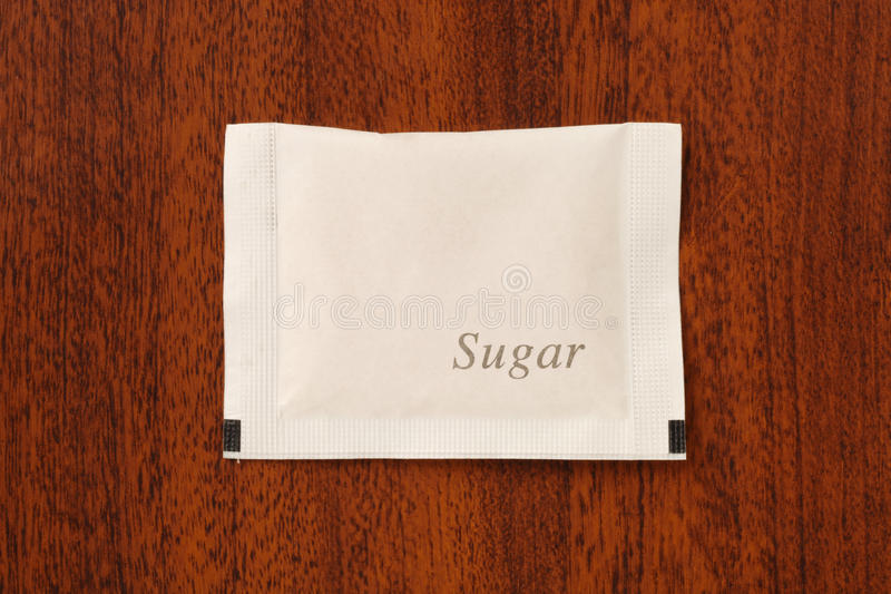 Sugar packet. On the wooden table stock images