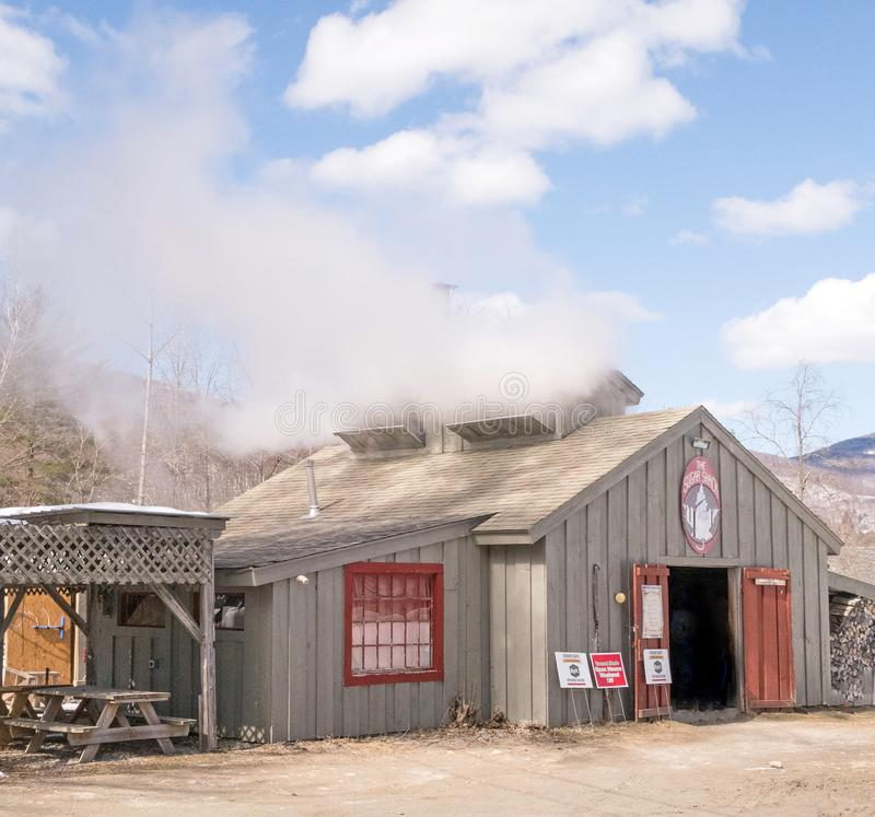 The Sugar Shack, Maple sugar shack. With smokestack during March springtime harvest, Arlington Vermont, New England with firewood and picnic tables during open stock photography