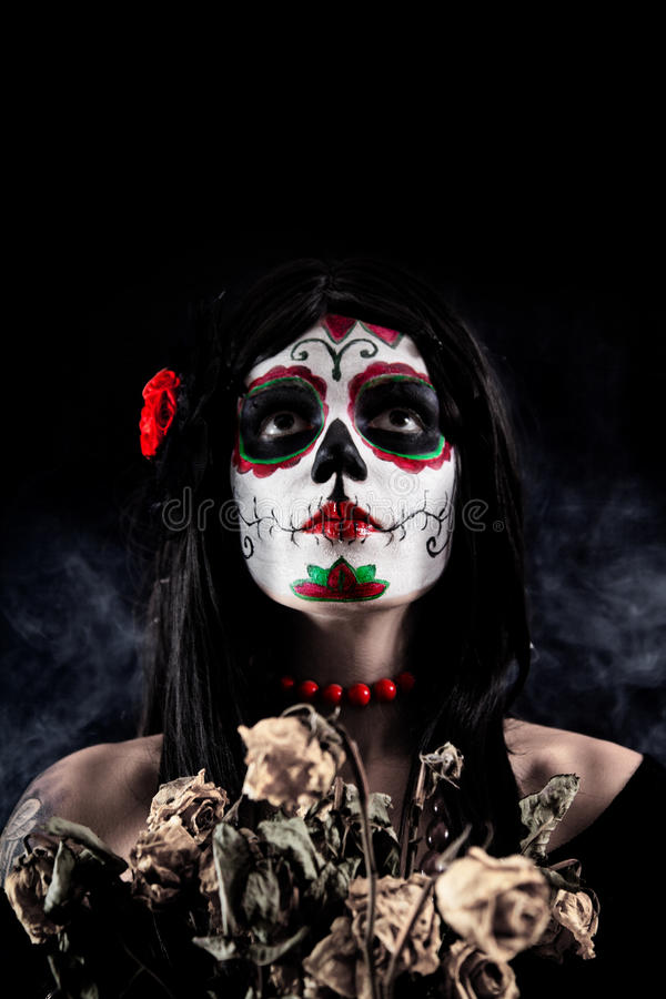 Sugar skull girl with dead roses. Studio shot over black smoky background stock photography