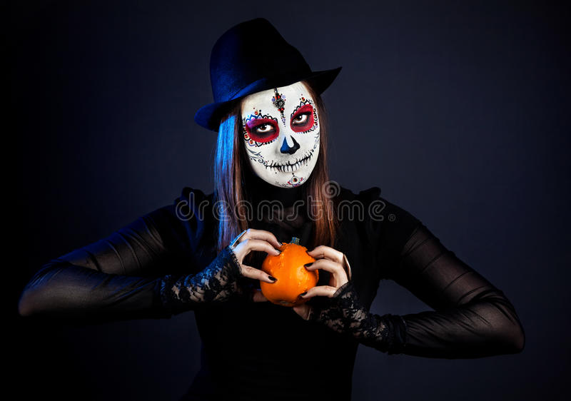 Sugar skull girl with pumpkin royalty free stock photography