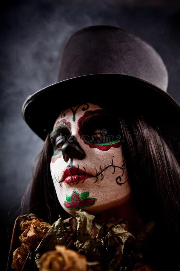 Sugar skull girl in tophat holding dead roses stock images