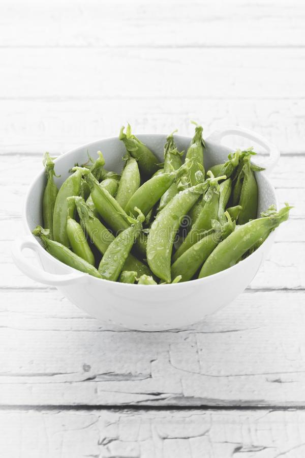 Sugar snap peas. Fresh green peas. Sugar snap peas Fresh green peas in the colanders on white wooden table royalty free stock photos