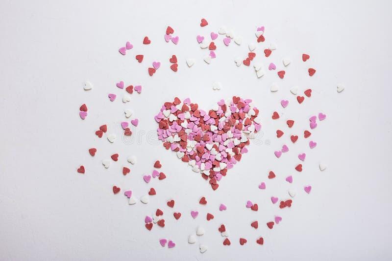 Sugar Sprinkles Candies in der Herz-Form zerstreut auf weißen Hintergrund Valentine Romance Birthday Charity Symbol stockfoto