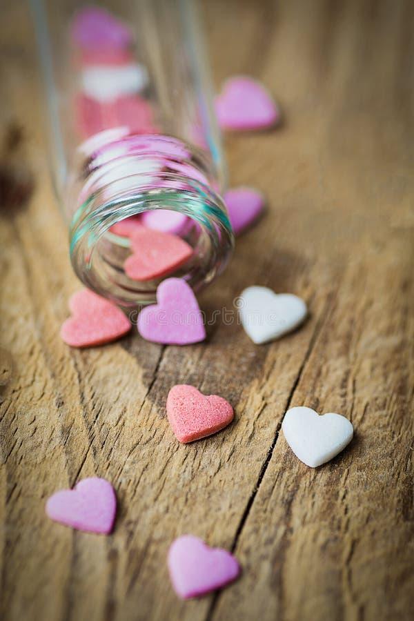 Sugar Sprinkles Candies Spilled blanc rouge-rose coloré de petite bouteille en verre sur le fond en bois superficiel par les agen images libres de droits