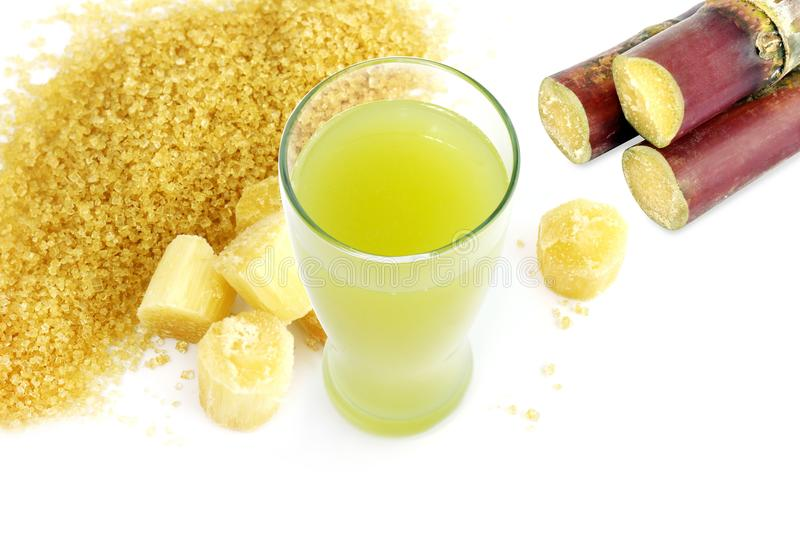 Sugar cane juice and fresh sugarcane cut, cane, granulated sugar yellow brown on white background royalty free stock photos