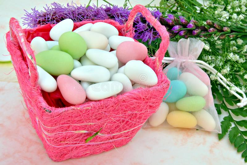 Sugared colors in a pink basket. With flowers in the background royalty free stock photo