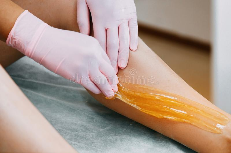 Sugaring Sugar waxing feet in the beauty salon. Depilation and beauty concept royalty free stock photo