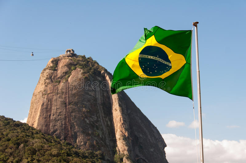 Sugarloaf Mountain and Brazil Flag. Waving Brazilian Flag and Sugarloaf Mountain Behind in Rio de Janeiro, Brazil royalty free stock photography