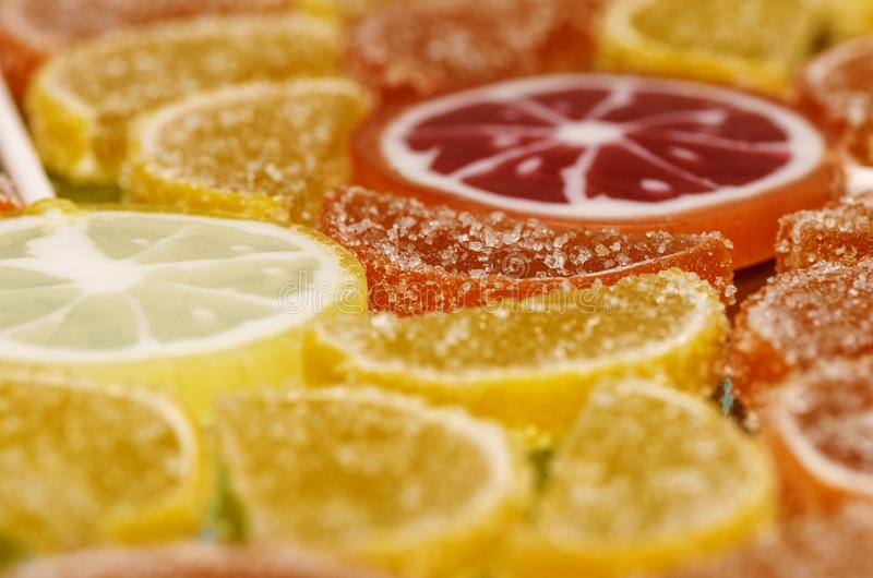 Sugary marmalade like lemon and orange slices with lollipops. Closeup macro candy background stock image