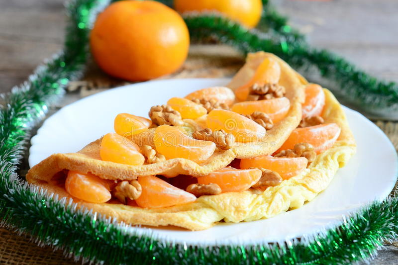 Sugary omelet on a plate. Homemade fried omelet stuffed with fresh mandarins and raw walnuts, green garland, fresh mandarins stock images