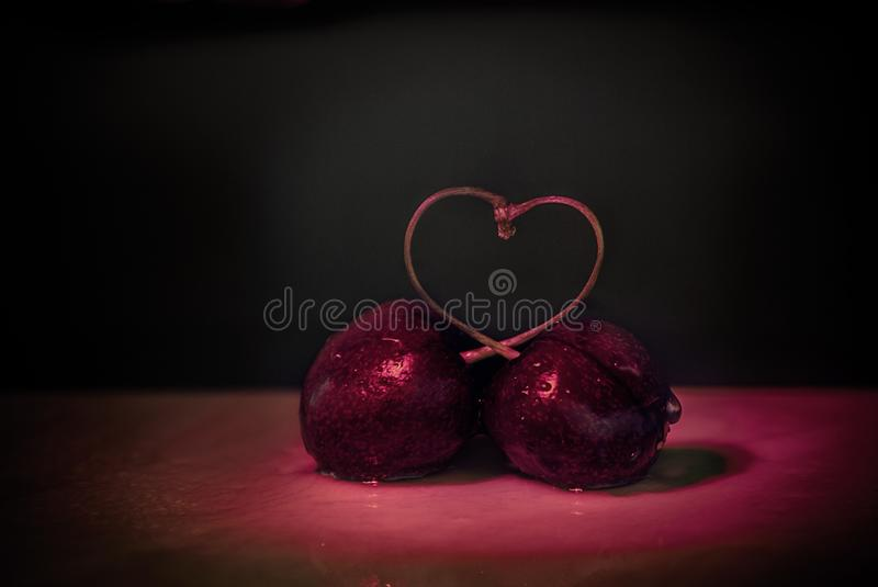 Natural Cherry love. Sugestive and evocative picture. It contains the shape of cherries heart in a dark red enviroment stock image
