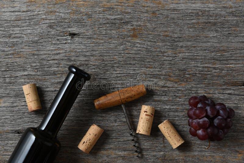 Sugheri, cavaturaccioli ed uva della bottiglia di vino su una vecchia tavola di legno rustica, con lo spazio della copia alla cim immagini stock