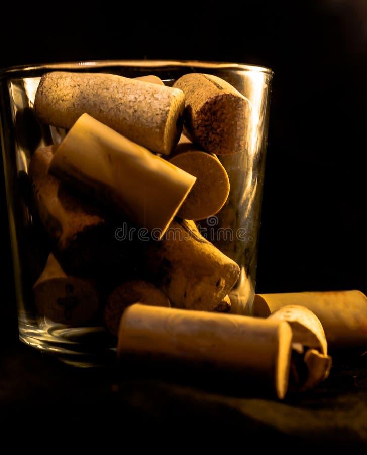 Sugheri del vino su un vetro fotografie stock