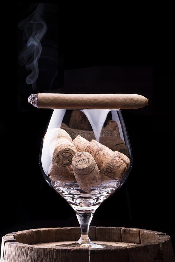Sugheri in vetro e sigaro del cognac sul nero fotografie stock libere da diritti