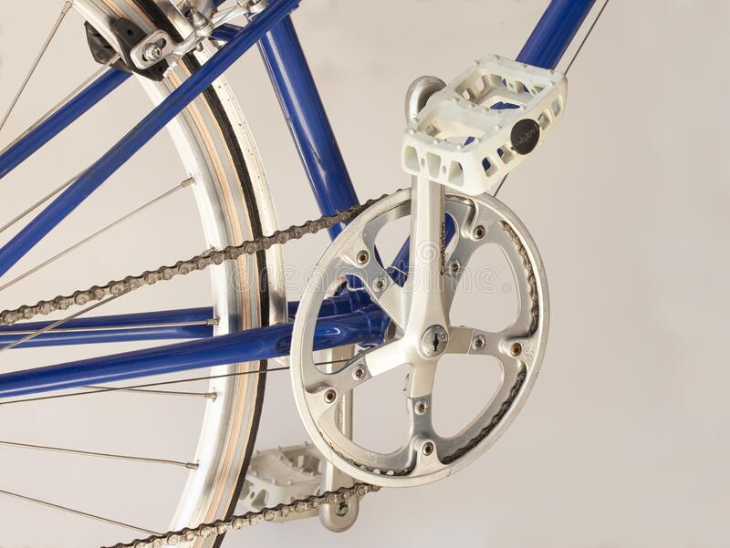 Sugino crankset, pedal and chain on a sporty blue bicycle. royalty free stock images
