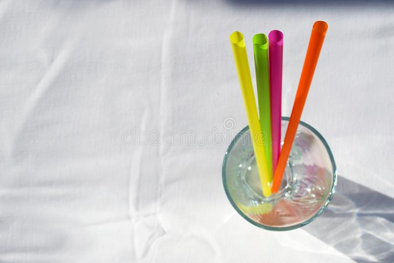 Sugrör i exponeringsglaset på den vita bakgrunden royaltyfri fotografi