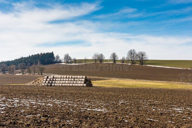 Sugrörbaler och gödsel på bygdfältet Vårfält och förberedelse för jordbruk Typisk tjeckiskt bygdland, tr royaltyfria bilder