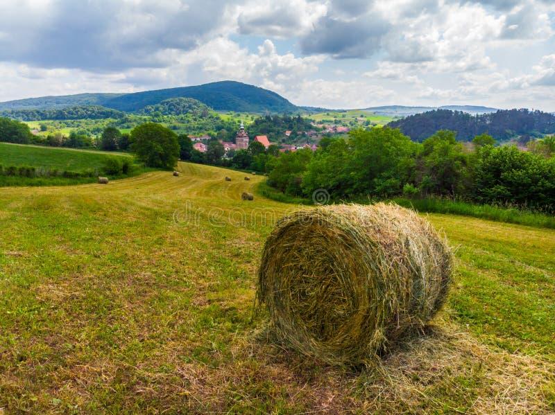 Sugrörbaler på fältet nära Saschiz stärkte kyrkan i Saschiz byar, Sibiu, Transylvania, Rumänien Åkerbrukt landskap, G royaltyfri fotografi
