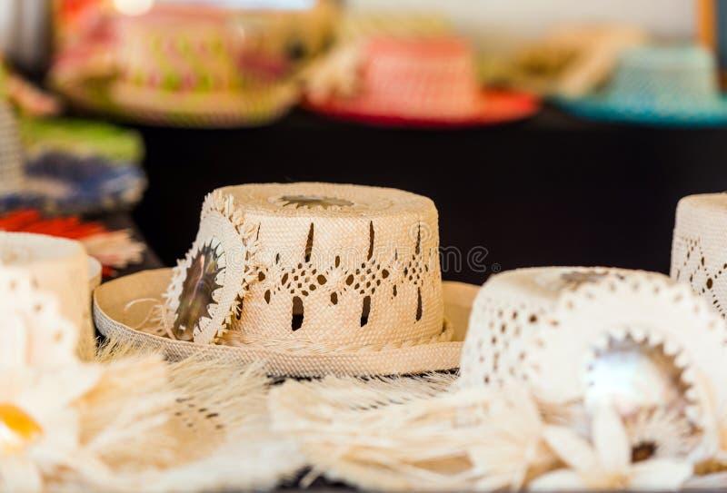 Sugrörhattar som är till salu i en tropisk souvenir, shoppar i Aitutaki, kocken Islands utomhus skjutit selektivt f?r fokus arkivbild