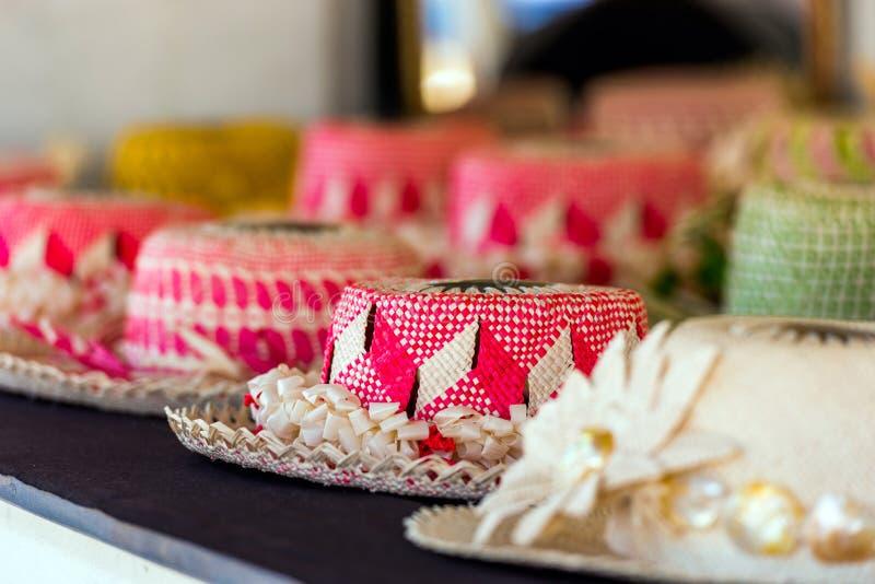 Sugrörhattar som är till salu i en tropisk souvenir, shoppar i Aitutaki, kocken Islands utomhus skjutit selektivt f?r fokus royaltyfri fotografi