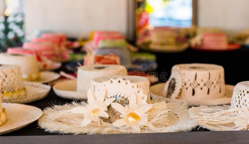 Sugrörhattar som är till salu i en tropisk souvenir, shoppar i Aitutaki, kocken Islands utomhus skjutit selektivt f?r fokus royaltyfri foto